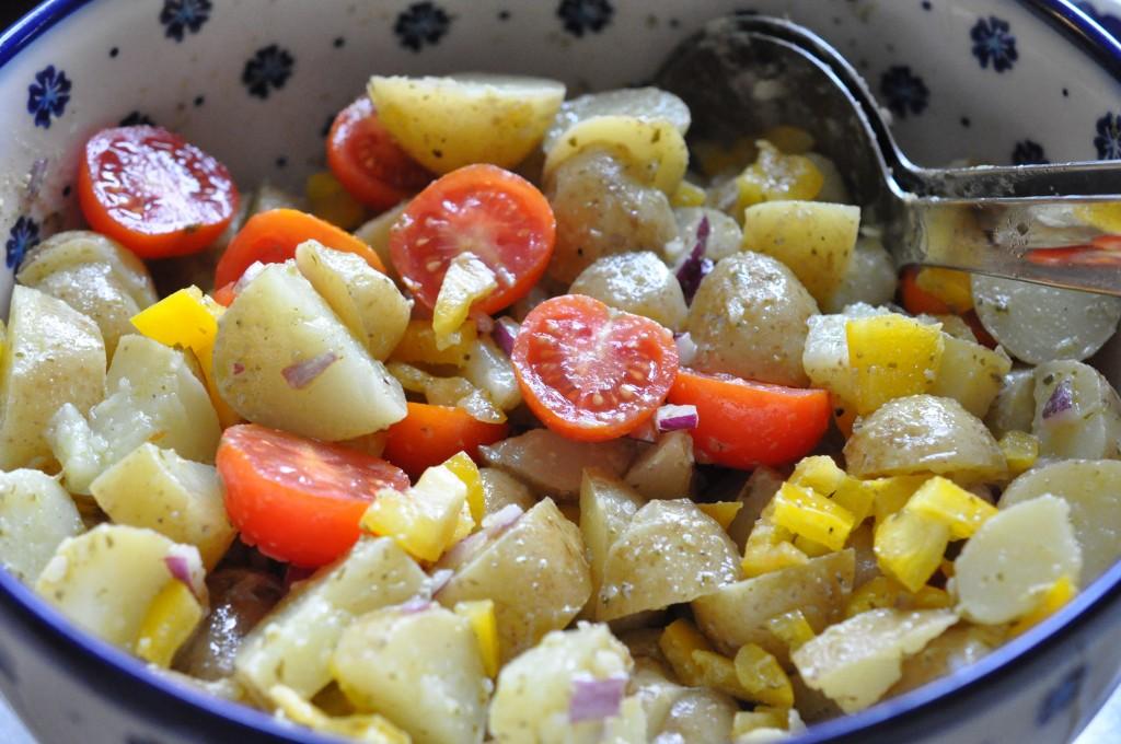 """Kartoffelsalat med pesto, rødløg & peberfrugt 1 kg nye kartofler (gerne små hurtige, der er købt vaskede) 1 finthakket peberfrugt (rød eller gul) 1 finthakket rødløg 250-300 gram cherrytomater Pesto marinade: 3 spsk. god olivenolie (f.eks. extra jomfru olivenkerne) 1 spsk pesto (rød eller grøn kan bruges) 1 spsk. hvidvinseddike eller citronsaft 1 tsk.dijonsennep Salt/peber Fremgangsmåde: Snit de kolde kogte kartofler Snit løg og peberfrugt. Bland kartofler og grønt Nu skal marinaden laves. Jeg havde en rest pesto i bunden af et glas. Jeg puttede olien heri og rystede glasset godt, så jeg kunne få al pestoen med. Jeg brugte min extra gode jomfruolienolie. Til en salat du skal spise """"au naturel"""" skal det helst være en god smagfuld olie (jeg bruger en billigere variant, til fødevarer jeg skal opvarme f.eks.) Jeg tilsatte 1 tsk sennep til pestodressingen og krydrede med salt og peber og hvidvinseddike, for at tilføre lidt syrlighed. Den blev HAMRENDE god den dressing! Tror jeg skal prøve den næste gang jeg skal ovnstege pestokartofler, sennepsmarinaden må også kunne bruges til varme kartoffelretter? Tja tjo kønt ser det ikke ud. Vi skal vist ikke tale om hvad det ligner her men LÆKKERT smager det! Har du en rest pesto, så smid den endelig ikke ud. Brug den i din dressing/marinade/gryderet (find selv på flere forslag..;-) Kartoffelsalaten vendes rundt med marinade og det hele. Vend forsigt, så kartoflerne ikke moses. Tilsæt tomater til sidst og lad gerne kartoffelsalaten trække lidt. Gerne 1 time inden servering (så lang tid kunne vi dog ikke vente i dag ;-)"""