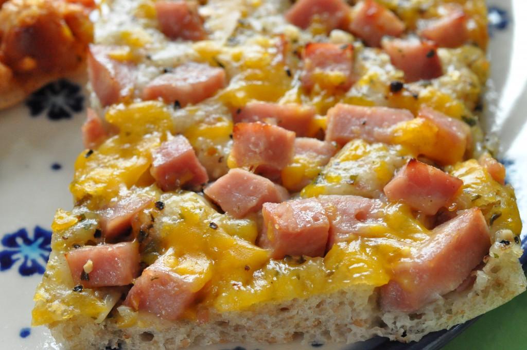 Pizza med skinke, hvidløgsolie, cocktailpølser og peberfrugtpesto
