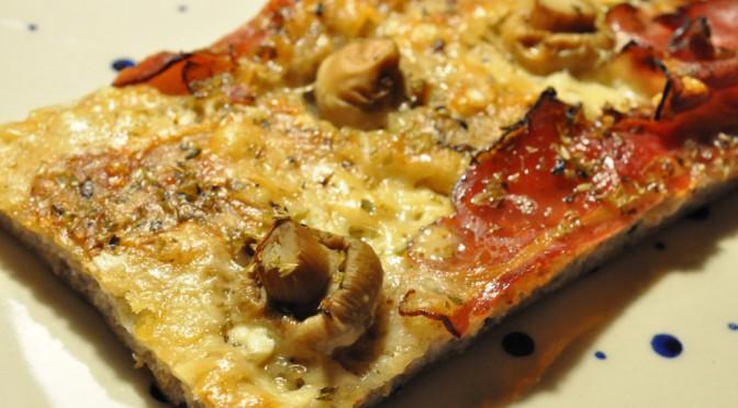 Grov pizza af koldthævet dej med parmesan og parmaskinke