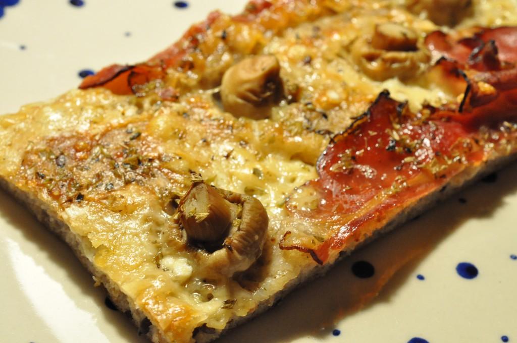 Grov pizza af koldthævet dej med parmesanost og parmaskinke