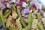 Marineret pastasalat med bønner, rødløg og tomat