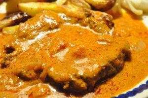 Steaks i flødesauce med tomat, løg og hvidløg